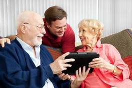 older couple and younger man studying computer