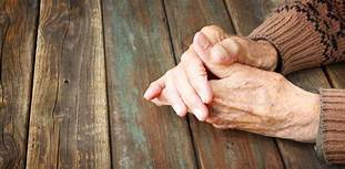 Old hands, clasped on table