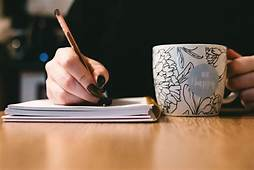 person writing; holding cup of coffee